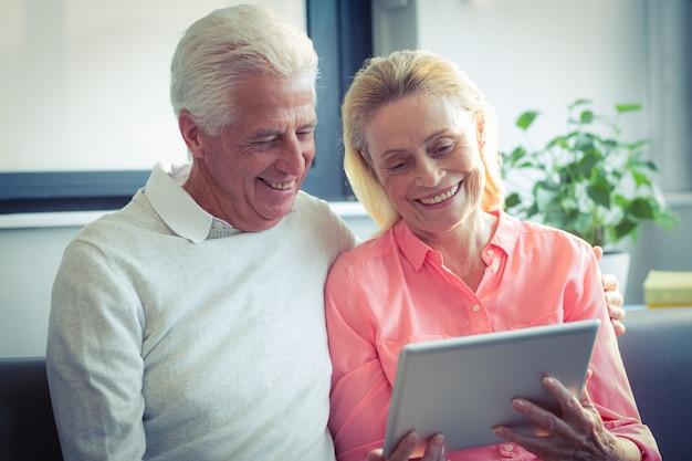 Starsza para ono uśmiecha się podczas gdy używać cyfrową pastylkę