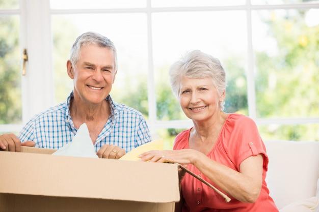 Starsza para otwiera dużego pudełko w żywym pokoju