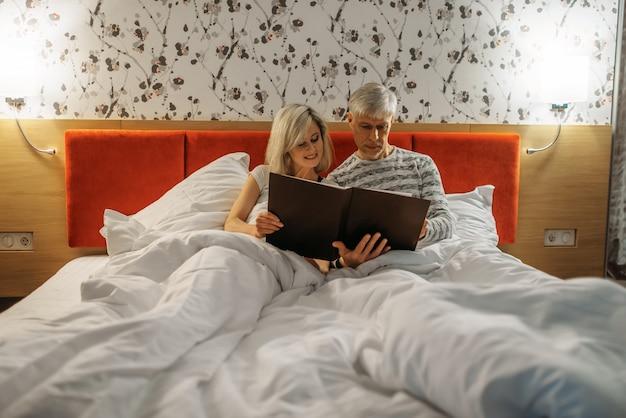 Starsza para patrząc na album ze zdjęciami w sypialni. mężczyzna i kobieta leżą w łóżku przed snem