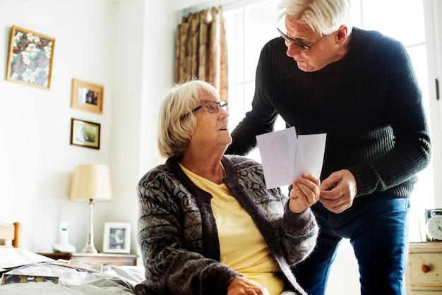 Starsza para patrzeje fotografie w pokoju wpólnie