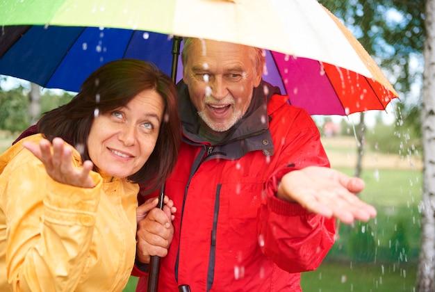 Starsza para pod tęczowym parasolem łapie kroplę deszczu