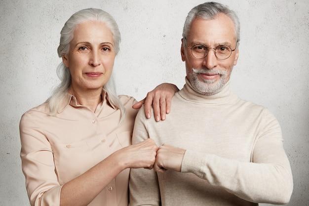 Starsza para pozuje przed betonową ścianą