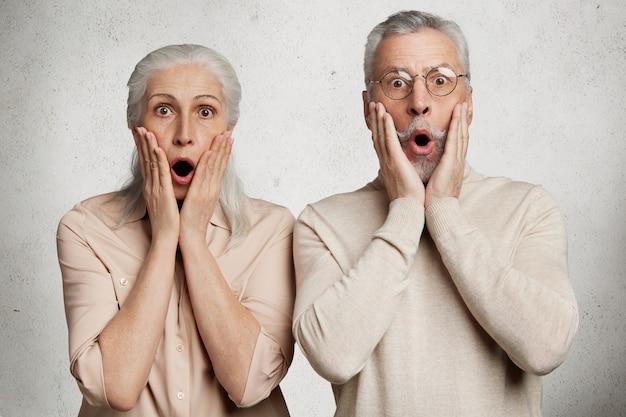 Starsza para pozuje przed białą betonową ścianą