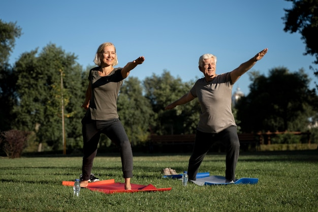 Starsza para praktykuje jogę na zewnątrz