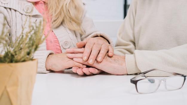 Starsza para przy stołowymi mienie rękami