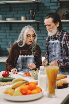 Starsza para przygotowuje jedzenie w kuchni