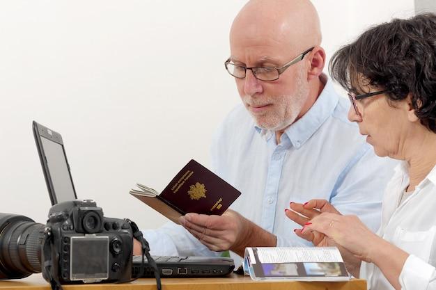 Starsza para przygotowywa urlopową wycieczkę z paszportem