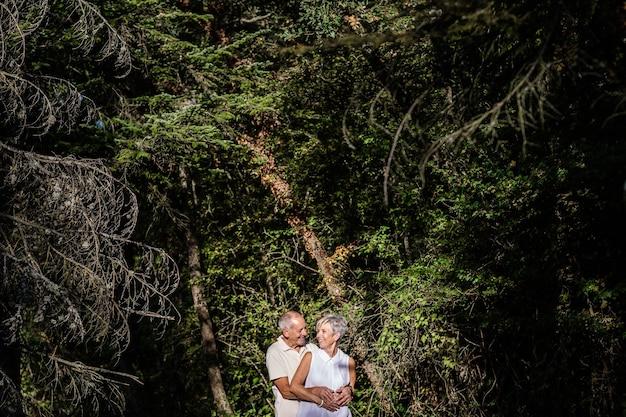 Starsza para radośnie obejmująca się wśród drzew w lesie podczas spaceru o zachodzie słońca.