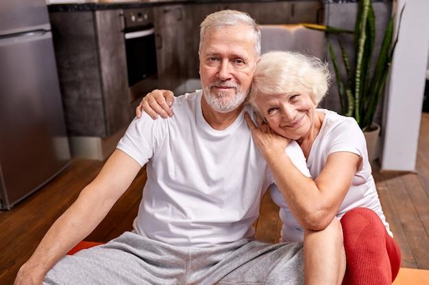 Starsza para relaks na podłodze po gimnastyce, uśmiechnięta, kobieta przytula mężczyznę