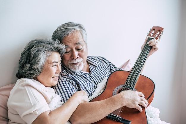 Starsza para relaksuje bawić się gitarę akustyczną w łóżkowym pokoju