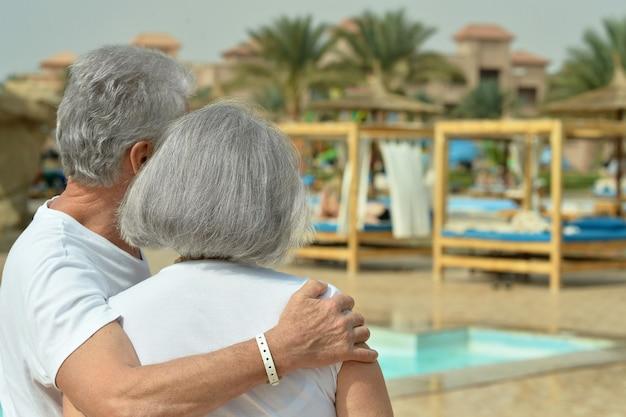 Starsza para relaksuje się w pobliżu basenu w ośrodku hotelowym, widok z tyłu