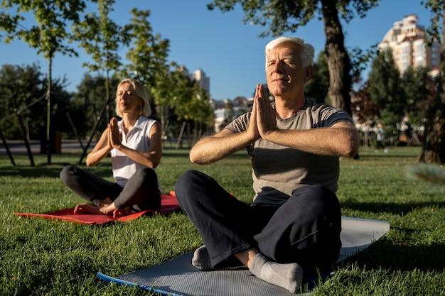 Starsza para robi joga na świeżym powietrzu