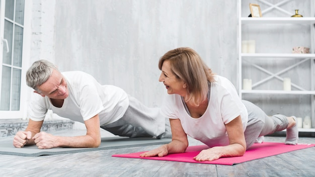 Starsza para robi joga wpólnie w domu