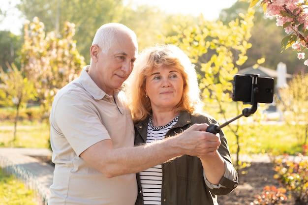 Starsza para robi selfie z selfie kijem na smartphone na naturze, nowożytny technologii pojęcie