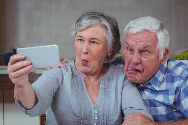 Starsza para robi twarzom podczas gdy brać selfie