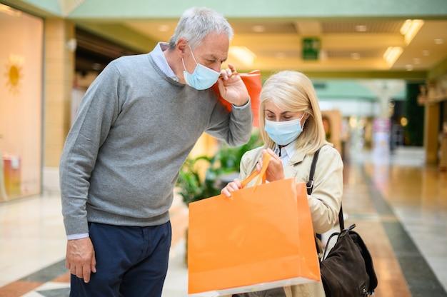 Starsza para robi zakupy w centrum handlowym w czasach koronawirusa, nosząc maski