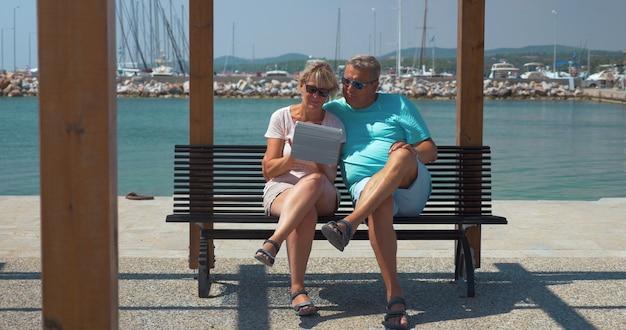Starsza para rodzinna z podkładką na nabrzeżu