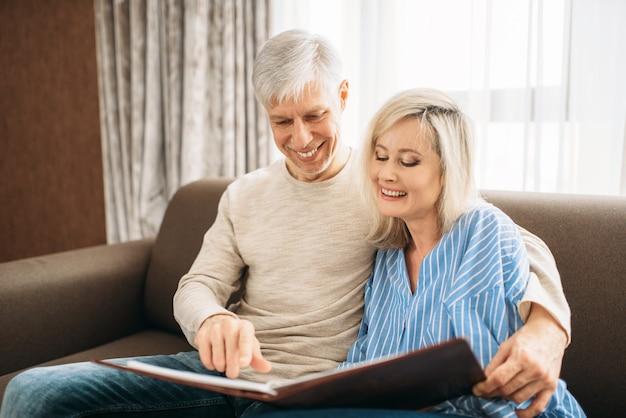 Starsza para siedzi na kanapie i patrząc na stary album ze zdjęciami, szczęśliwa rodzina. dorosły mąż i żona odpoczywają w domu