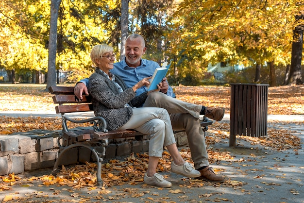 Starsza para siedzi na ławce i czyta książkę w parku
