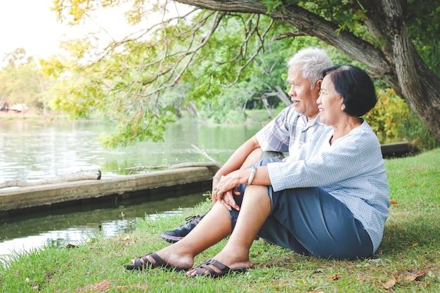 Starsza para siedzi nad stawem w parku. koncepcja społeczności zdrowego starzenia się