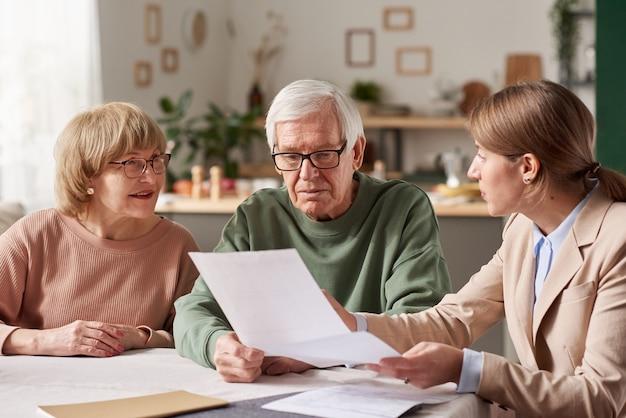 Starsza para siedzi przy stole i omawia dokumenty z agentem nieruchomości, który sporządza testament