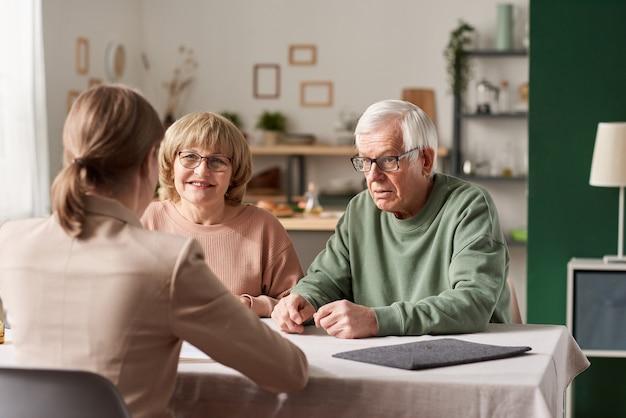 Starsza para siedzi przy stole z pośrednikiem w handlu nieruchomościami i konsultuje się w sprawie dokumentów finansowych w domu
