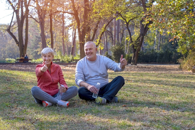Starsza para siedzi szczęśliwie na trawie w parku, trzymając kciuki do góry w ciągu dnia