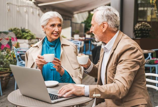 Starsza para siedzi w restauracji z laptopa