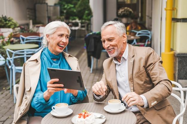 Starsza para siedzi w restauracji z tabletem