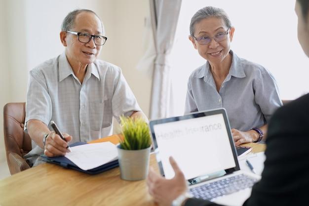 Starsza para słucha ubezpieczenie zdrowotne sprzedawcą.