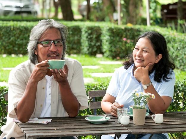 Starsza para śmia się podczas gdy pijący kawę w domu ogródzie.