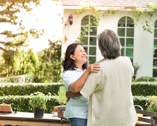 Starsza para śmia się wpólnie w domu ogródzie.