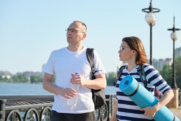 Starsza para spacerująca i rozmawiająca mężczyzna i kobieta, ludzie ubrani w stroje sportowe idący na trening fitness, aktywny zdrowy tryb życia i związki w wieku 40 lat
