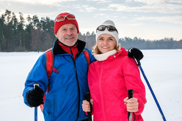 Starsza para spacerująca z kijkami do nordic walking w śnieżnym zimowym parku