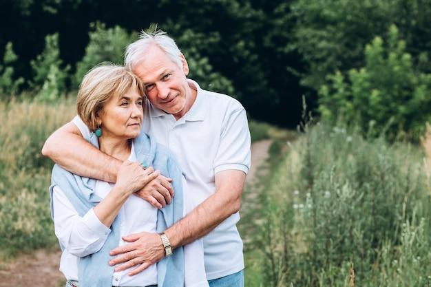 Starsza para spaceruje w naturze i przytula