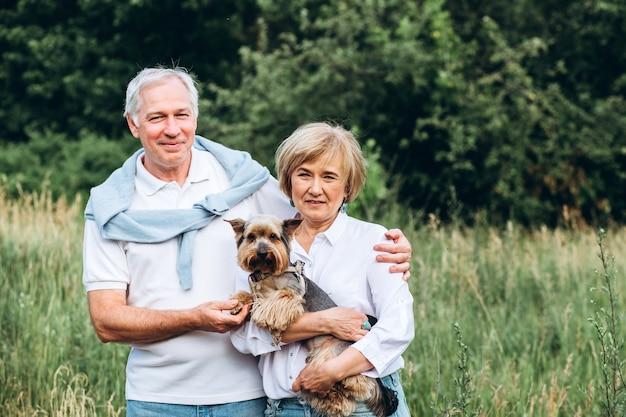 Starsza para spaceruje w przyrodzie z małym psem