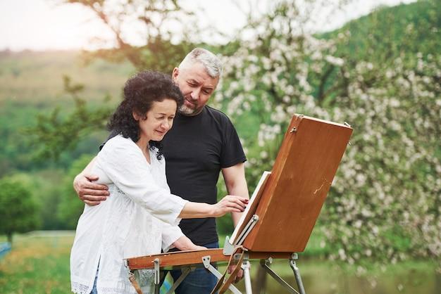 Starsza para spędza wolny czas i razem pracuje nad farbą w parku