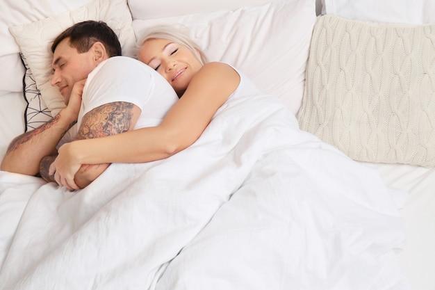 Starsza para śpi w łóżku