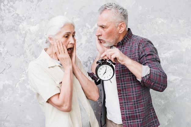 Starsza para trzyma zegar