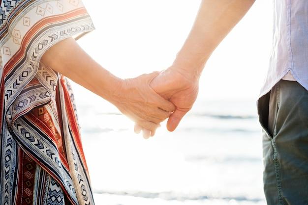 Starsza para trzymając się za ręce na plaży