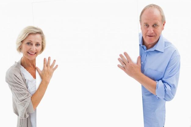 Starsza para uśmiecha się i trzyma karty