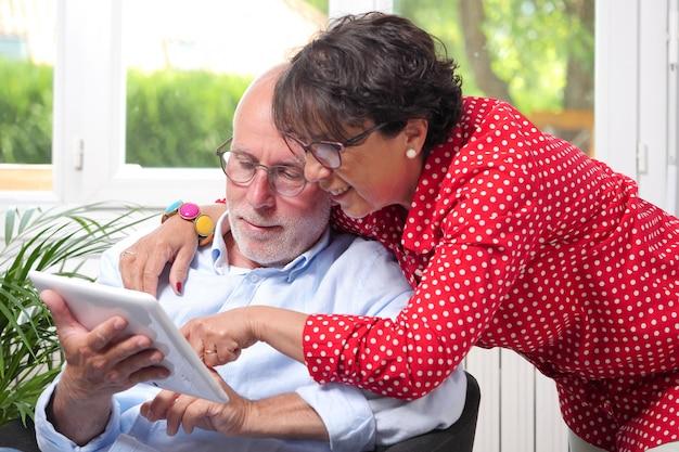 Starsza para używa cyfrową pastylkę w domu