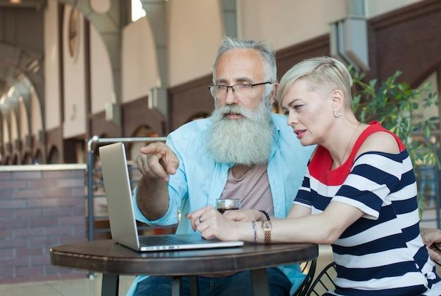 Starsza para używa laptop w kawiarni wpólnie