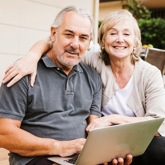 Starsza para używa laptop w ogródzie