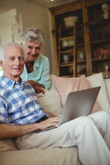 Starsza para używa laptop w żywym pokoju