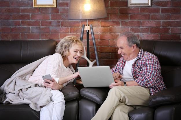 Starsza para używa laptopa i telefonu komórkowego razem w domu