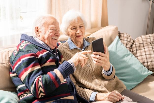Starsza para używa smartphone w pomieszczeniu