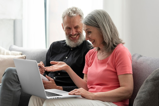 Starsza para w domu na kanapie przy laptopie