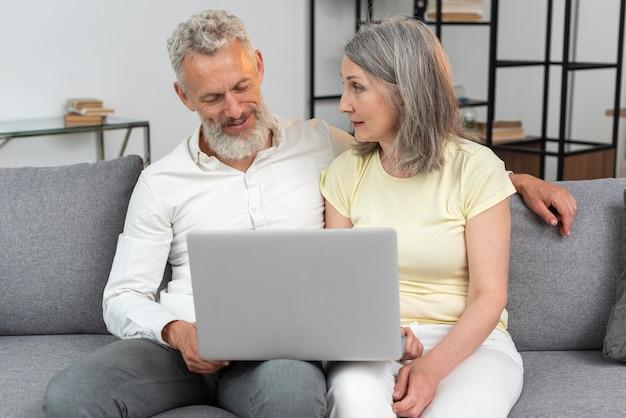 Starsza para w domu na kanapie za pomocą laptopa