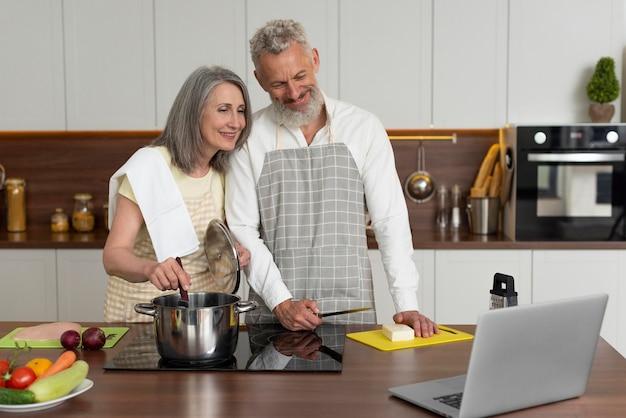 Starsza para w domu w kuchni biorąc lekcje gotowania na laptopie